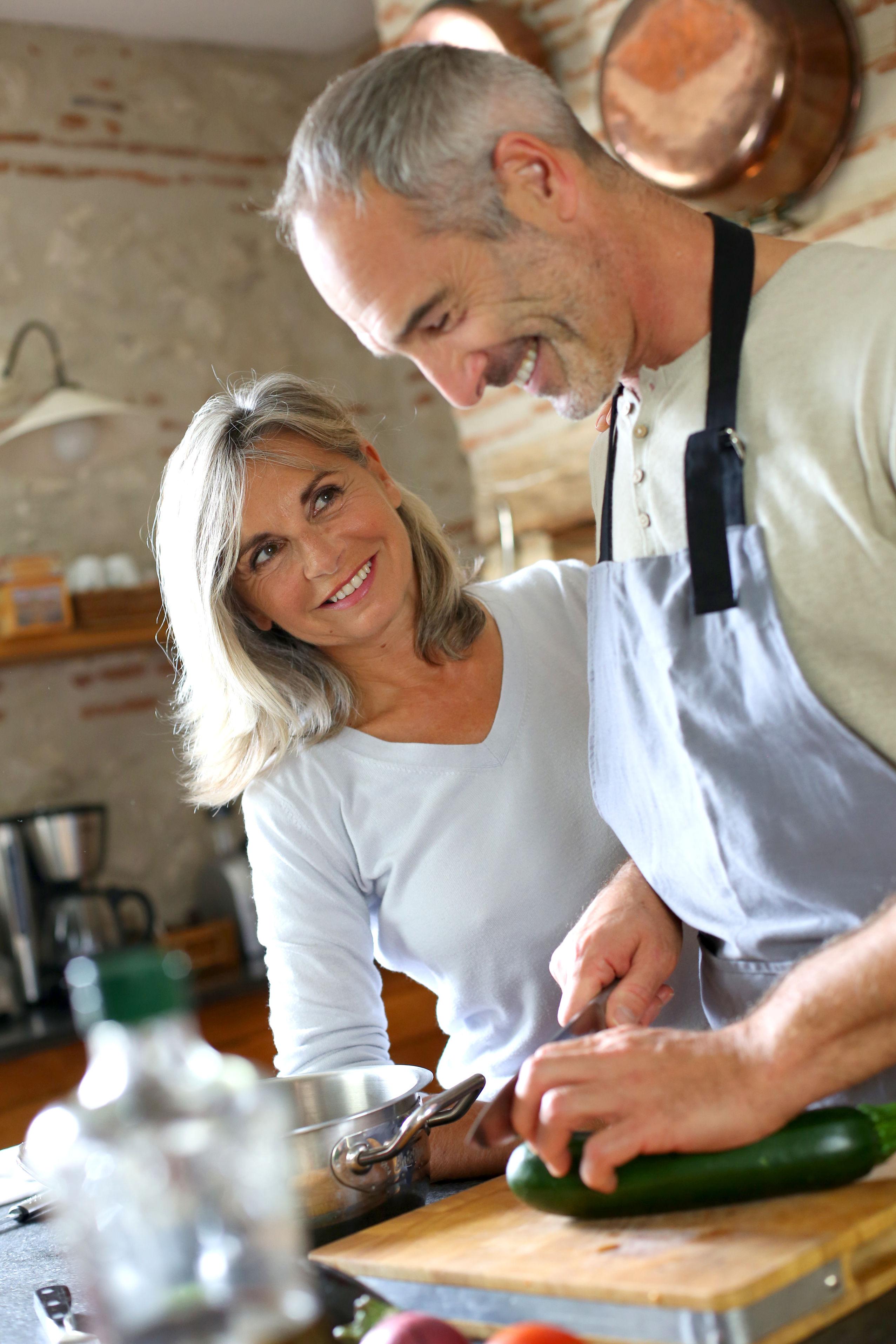 22417892 - senior couple in kitchen preparing dinner